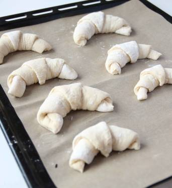 4. Böj rullarna något och lägg dem på en plåt med bakplåtspapper. Låt dem jäsa under bakduk i ca 30 min. Sätt ugnen på 230 grader.