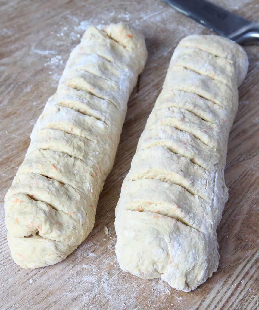 2. Knåda igenom degen på ett mjölat bakbord. Dela degen i två delar och forma två limpor av dem. Skär några snitt i dem med en vass kniv. Strö över lite mjöl.