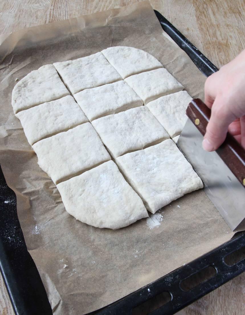 3. Dela degen i ett rutmönster, 16 st, med en degskrapa eller kniv. Strö över lite vetemjöl och låt den jäsa under bakduk i ca 30 min. Sätt ugnen på 230 grader. Grädda brödet mitt i ugnen i 15–20 min.