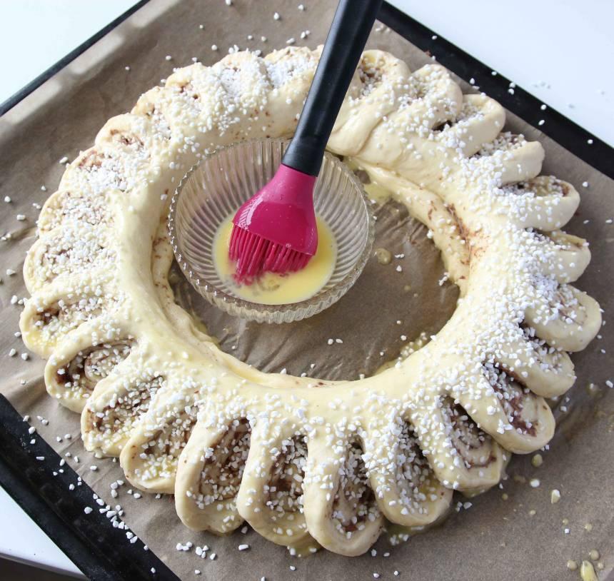 4. Pensla kransen med ägg och strö över pärlsocker. Grädda kransen längst ner i ugnen i 30–35 min. Låt den svalna på plåten.
