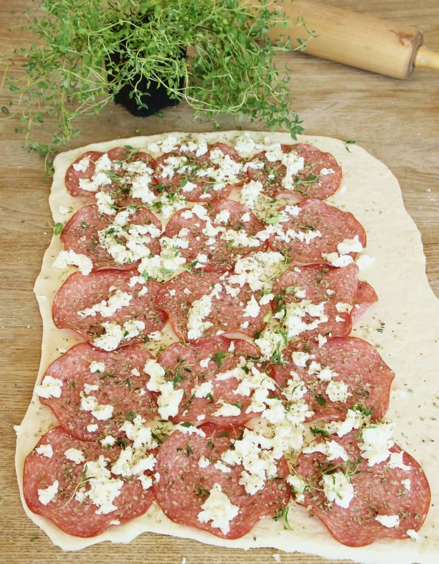 3. Lägg ut hälften av salamiskivorna, oregano och smulad mozzarella på varje degplatta.