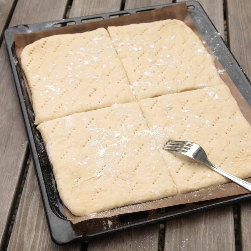 4. Skär degen med en vass kniv eller en degskrapa i fyra delar. Nagga degen med en gaffel. Strö över lite vetemjöl. Låt bröden jäsa under bakduk i ca 30 min. Sätt ugnen på 225 grader.