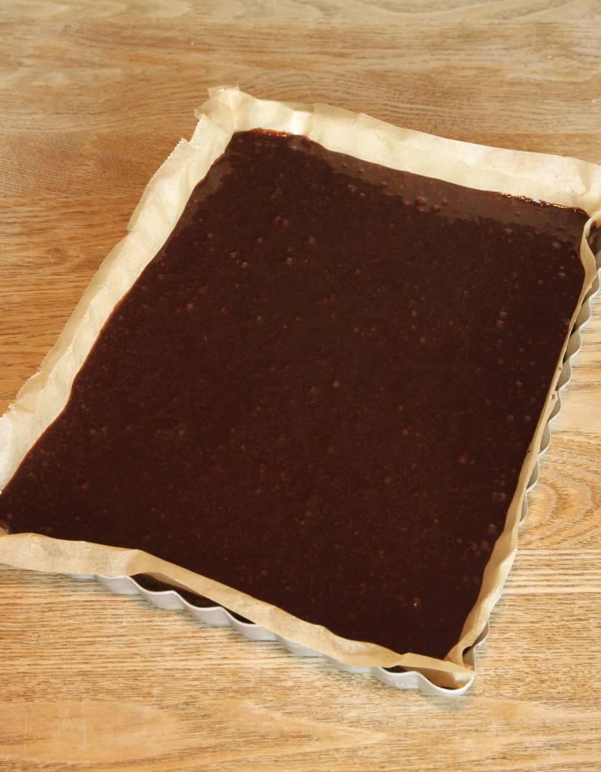 2. Lägg i ett bakplåtspapper i en form, ca 18 x 25 cm eller smörj och bröa den. Häll smeten i formen och bred ut den med en slickepott. Grädda kakan mitt i ugnen i 20–25 min. Låt den svalna i formen.