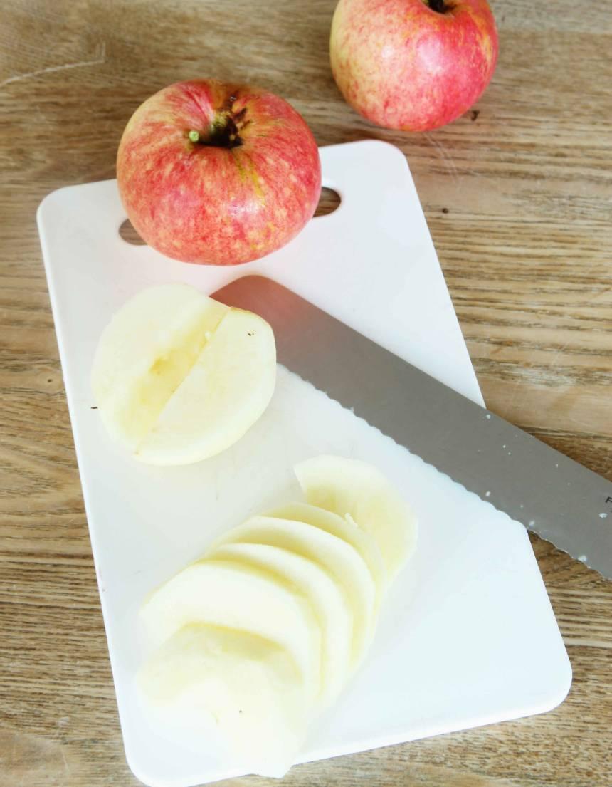 3. Skala äpplena, ta ur kärnhuset och dela dem på mitten. Skär äpplena i skivor, ca ½ cm tjocka.