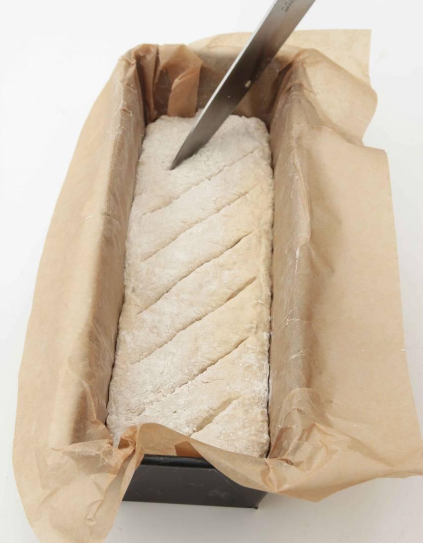 3. Forma resten av degen (1/3) till en limpa och lägg den i en limpform, ca 1 ½ liter, klädd med bakplåtspapper. Snitta ytan på limpan med en vass kniv. Låt bröden jäsa under bakduk i ca 30 min. Sätt ugnen på 230 grader.