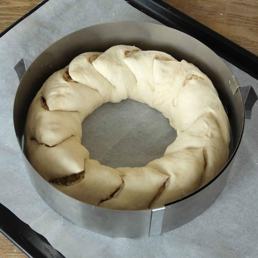 6. Knäpp upp kanten på en springform och lägg den runt degen för att ge kransen en jämn, fin form under gräddningen. Låt kransen jäsa under bakduk i ca 30 min. Sätt ugnen på 200 grader.