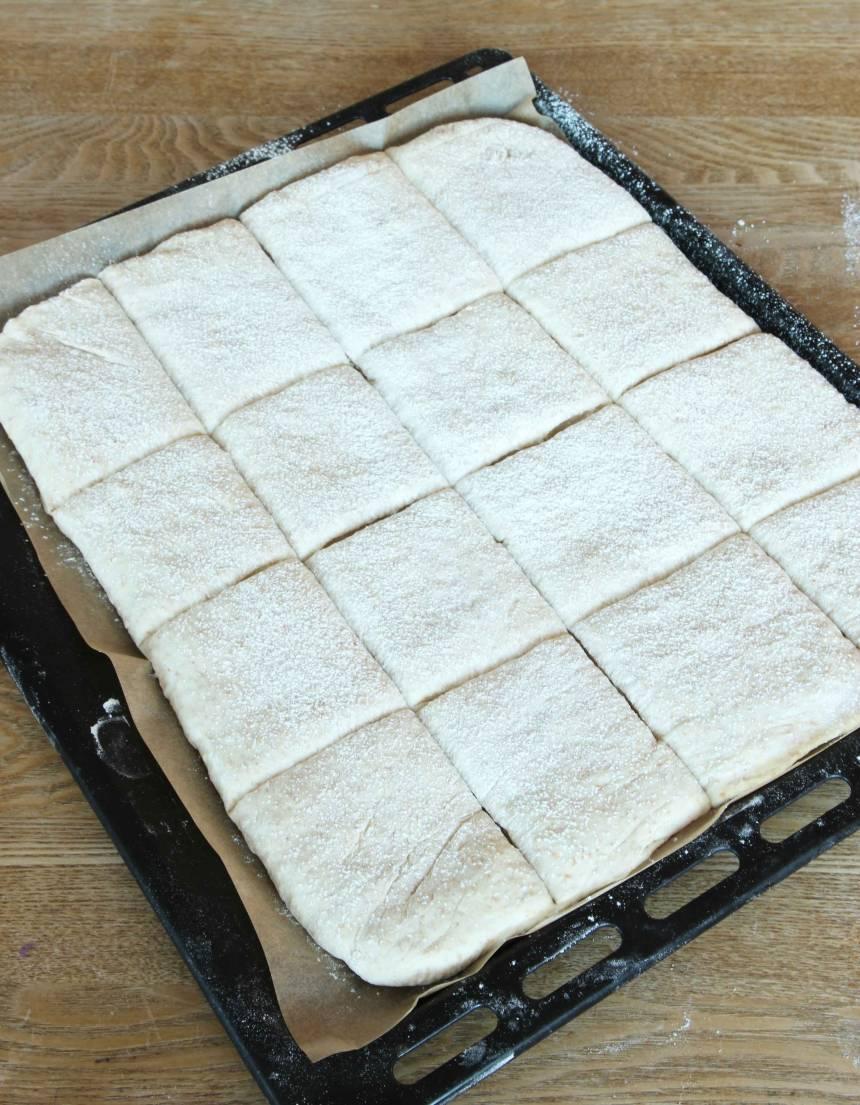 3. Tryck ut degen på en ugnsplåt med bakplåtspapper. Skär den i rutor, 5 x 4 centimeter. Pudra över vetemjöl med en sil. Täck degen med plastfolie och ställ den i kylskåpet över natten.