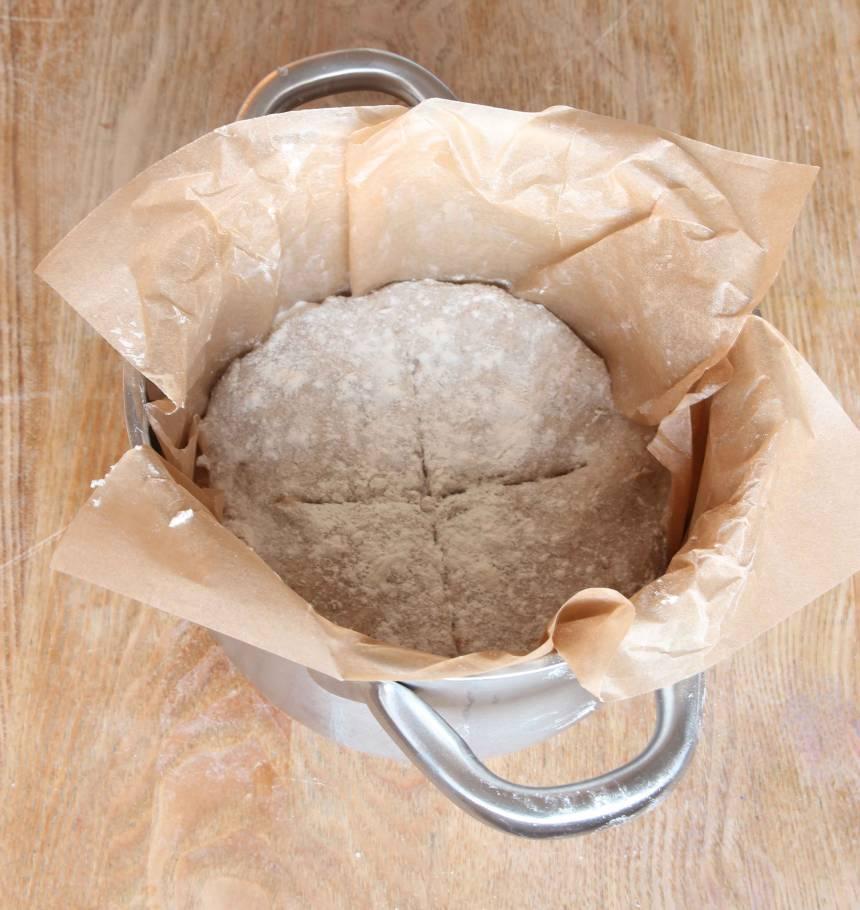 2. Knåda ihop degen till en boll och rulla den i mjöl. Lägg degen i en kastrull, ca 3 liter, klädd med bakplåtspapper. Snitta ett kors i degen med en vass kniv. Lägg på ett lock och låt degen jäsa i kastrullen i kylskåpet över natten.