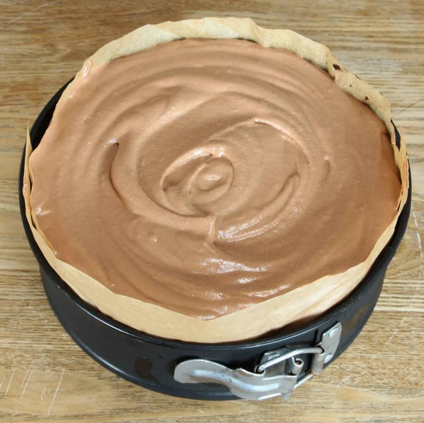 4. Chokladmousse: Koka upp grädden i en kastrull. Häll den över chokladen i en skål och rör om till en slät smet. 5. Koka upp socker och vatten. Stäng av plattan. Tillsätt äggulorna och vispa kraftigt med en elvisp till en krämig smet. 6. Vispa grädden lätt och blanda den försiktigt med äggsmeten och chokladsmeten. Bred ut moussen över bottnen. Ställ kakan i frysen i 3–4 tim. Ta fram kakan, strö över hyvlad choklad och servera den rumstempererad. Förvara kakan i kylen.
