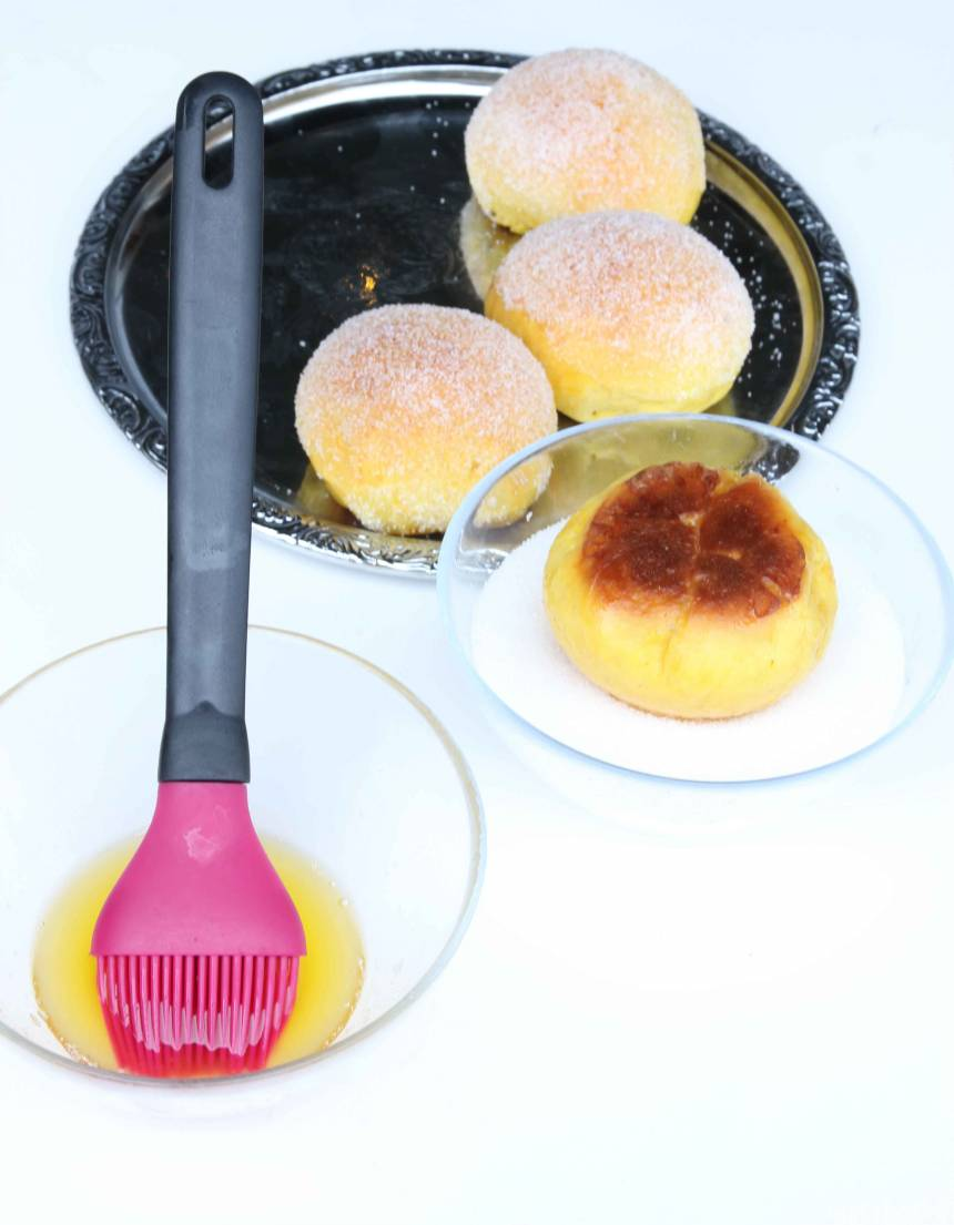 5. Pensla bullarna med smält smör medan de fortfarande är varma och doppa dem i strösocker. Låt dem svalna på en plåt eller galler.