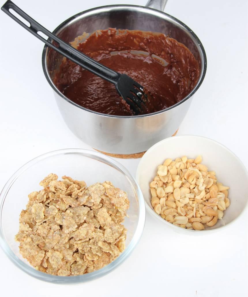 2. Krama sönder flingorna lite lätt och grovhacka nötterna. Blanda ner dem i nougatsmeten.