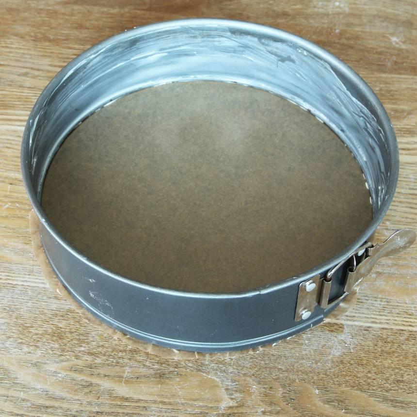 2. Smörj kanten på en springform, ca 24 cm i diameter. Kläm fast ett bakplåtspapper i botten och klipp bort kanterna som sticker ut. Knäpp upp formen igen.