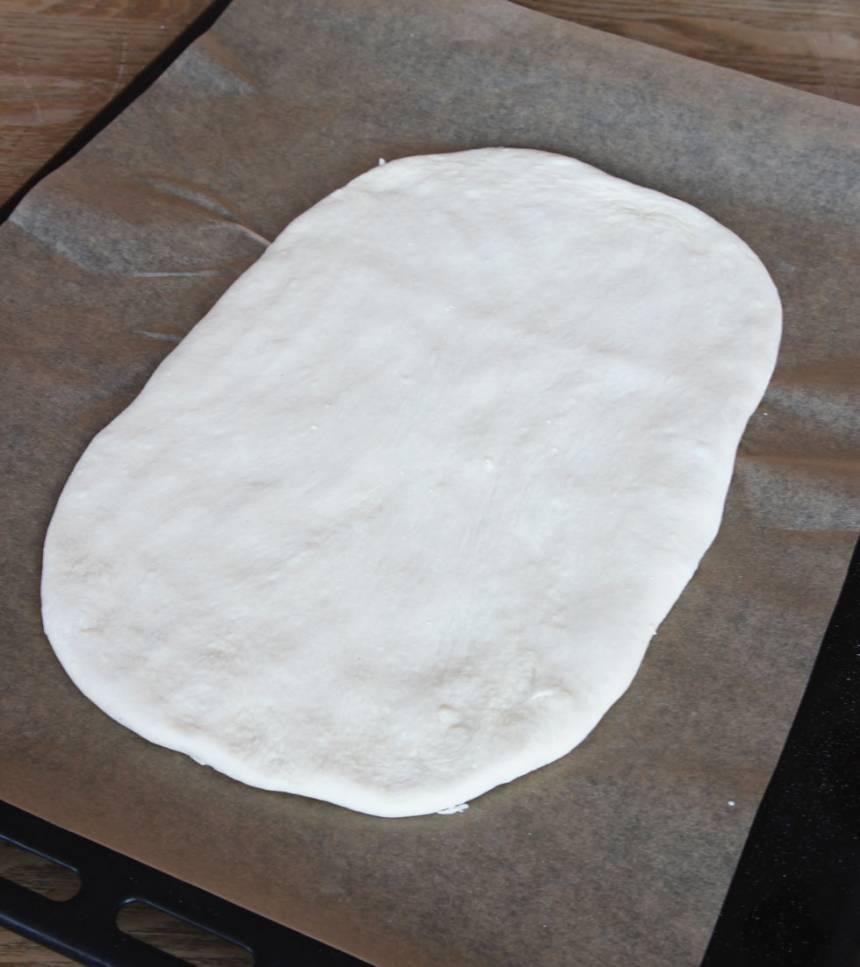 2. Tryck ut degen på en plåt med bakplåtspapper, 1 1/2–2 cm tjock. Låt den jäsa under bakduk i 50–60 min. Sätt ugnen på 230 grader.
