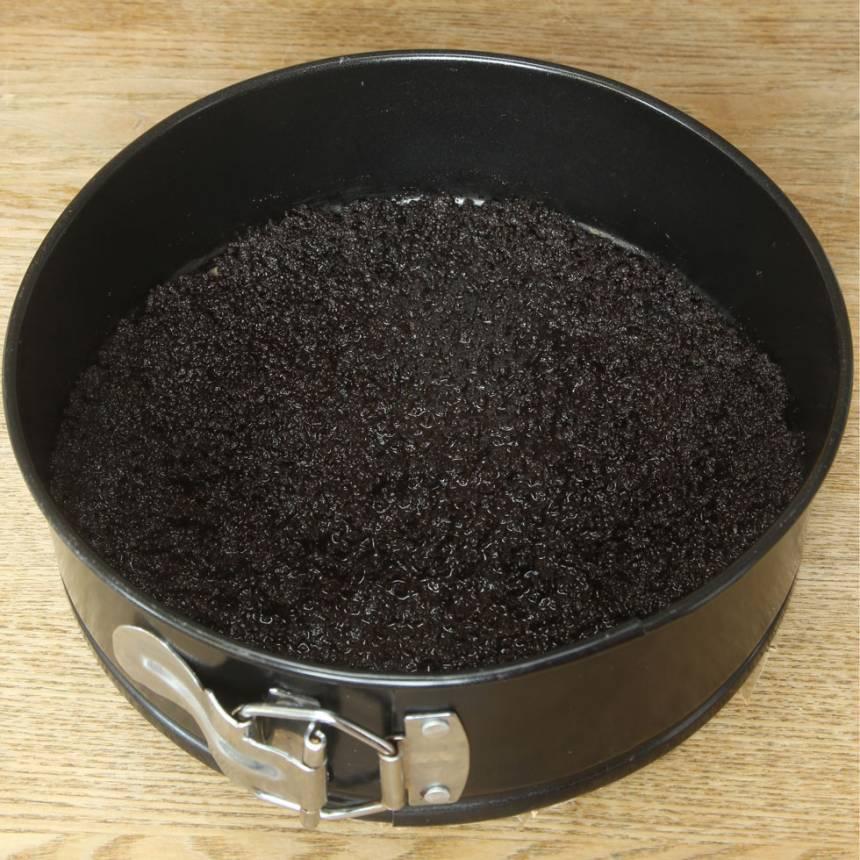 2. Sätt fast ett bakplåtspapper i botten på en springform, ca 23 cm i diameter. Tryck ut smulorna i bottnen. Ställ den i frysen i ca 30 min för att stelna.