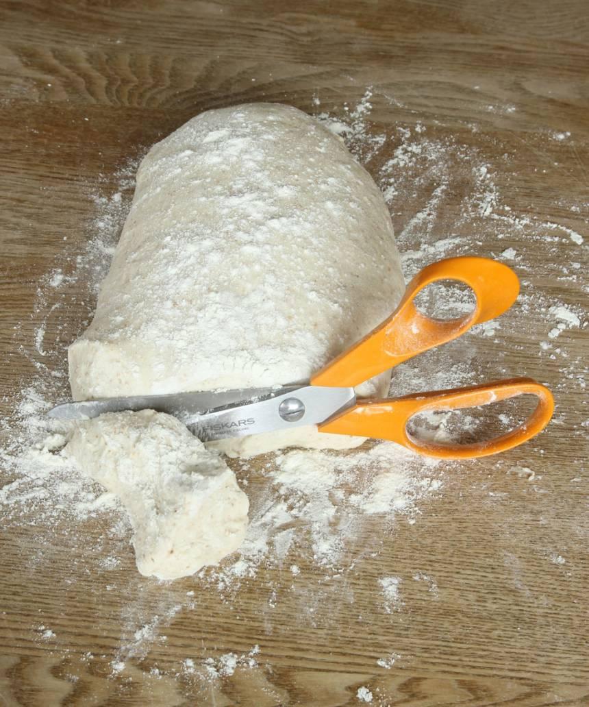 2. På morgonen: Knåda snabbt ihop degen på ett mjölat bakbord. Klipp 14–16 degbitar med en sax.