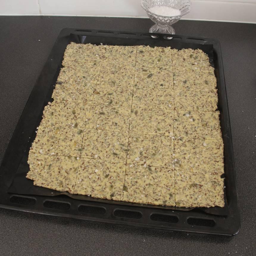 4. Lägg det undre pappret med degen på en ugnsplåt. Skär degen i ett rutmönster, 24–28 bitar. Strö över lite flingsalt. Grädda brödet mitt i ugnen i ca 60 min. Låt det stå kvar i eftervärmen om det inte stelnat i mitten. Låt det svalna på plåten.