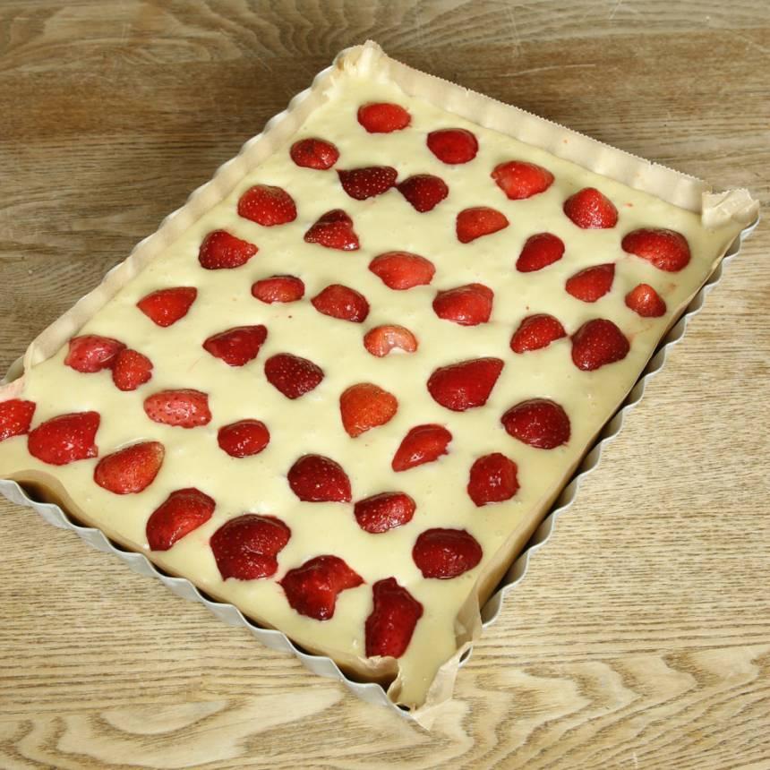 3. Häll smeten i en smord och bröad form eller klädd med bakplåtspapper, 19 x 26 cm eller en rund springform, ca 23 cm. Lägg jordgubbsbitarna ovanpå smeten.