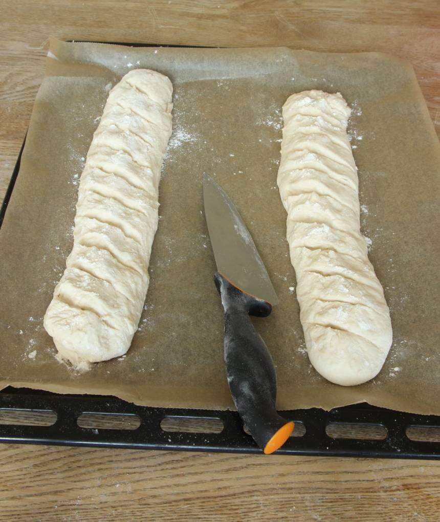 3. Lägg baguetterna på en ugnsplåt klädd med bakplåtspapper. Skär sneda snitt i baguetterna med en vass kniv. Låt dem jäsa under bakduk i ca 30 min. Sätt ugnen på 250 grader.