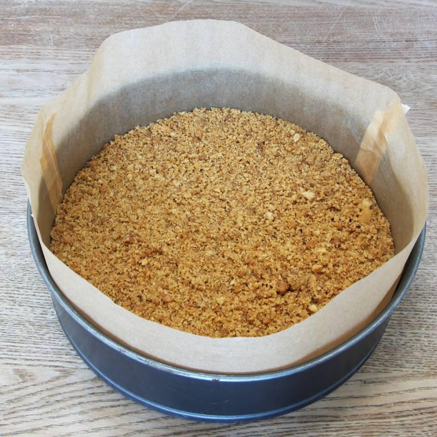 2. Tryck fast ett bakplåtspapper i en springform, 23–24 cm i diameter. Klipp en bred remsa bakplåtspapper och klä kanten med det. Tryck ut smulorna i bottnen. Ställ formen i frysen i ca 20 min.