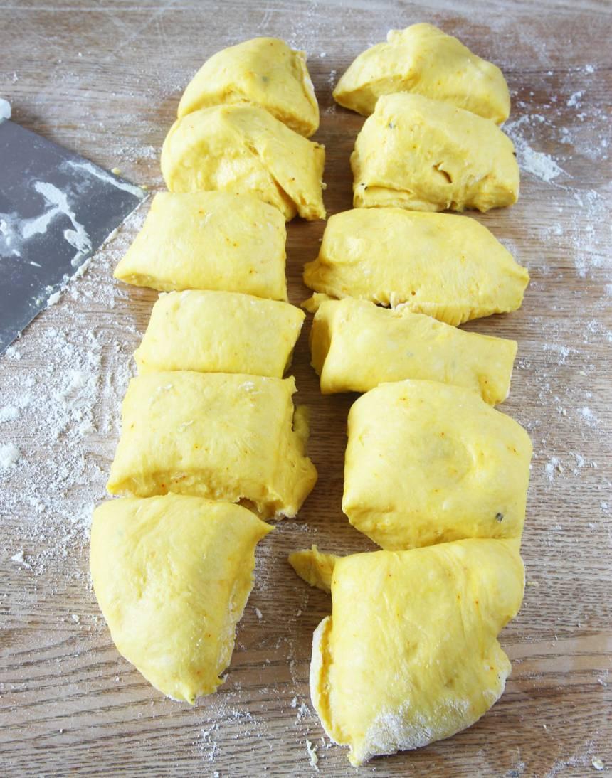 2. Knåda igenom degen på ett mjölat bakbord och dela den i 12 bitar.