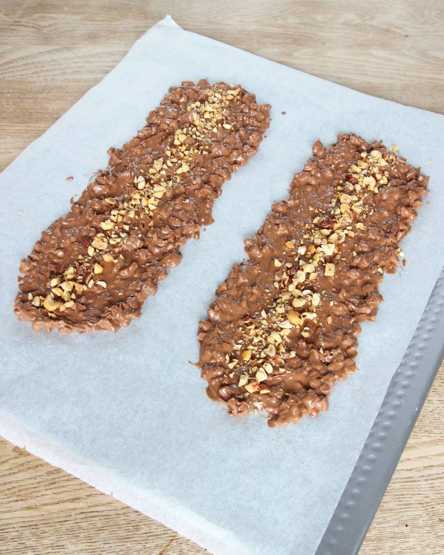 6. Bred ut chokladen till två längder på ett bakplåtspapper. Strö över resten av hasselnötterna. Låt chokladen stelna i kylen. Förvara bräcken i kylen för den kan mjukna i rumsvärme.