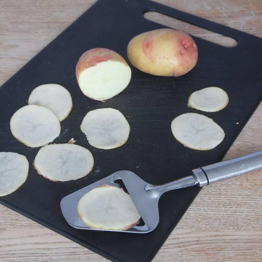 2. Tvätta potatisarna noga och torka dem torra. Skiva potatisarna tunt med en osthyvel.