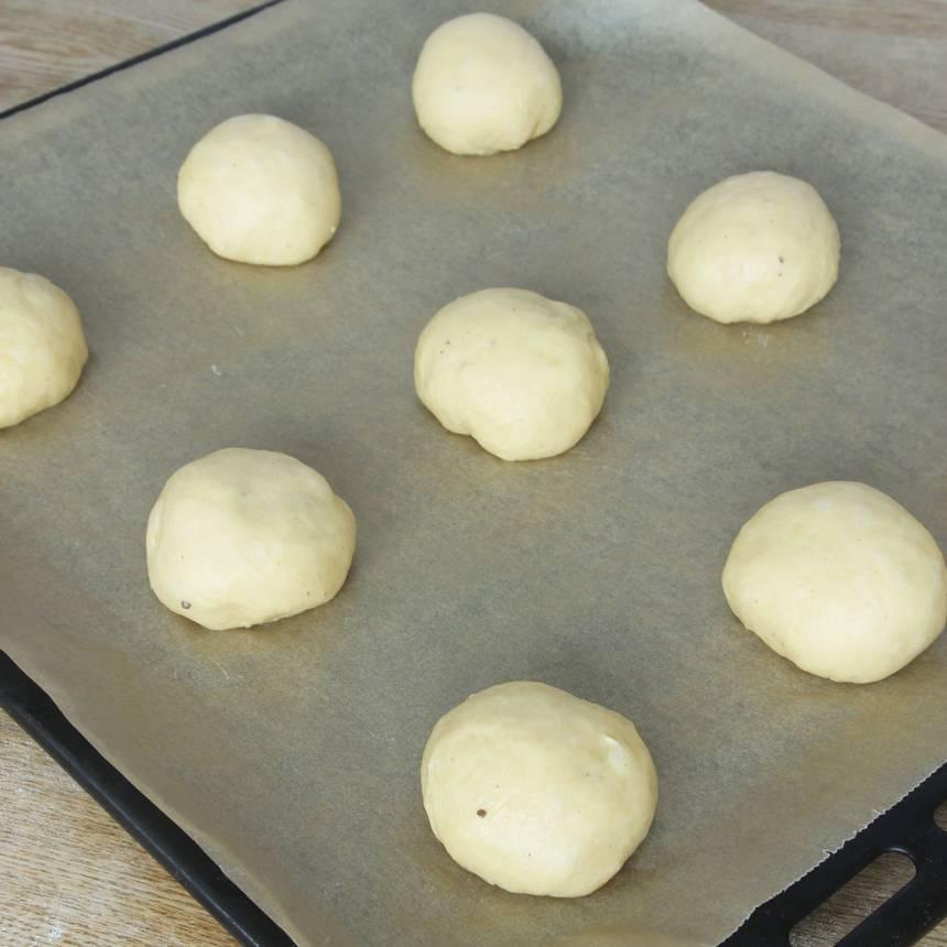 2. Knåda igenom degen på ett mjölat bakbord och dela den i ca 30 bitar. Forma släta bullar och lägg dem på en plåt med bakplåtspapper. Låt dem jäsa under bakduk i ca 45 min.