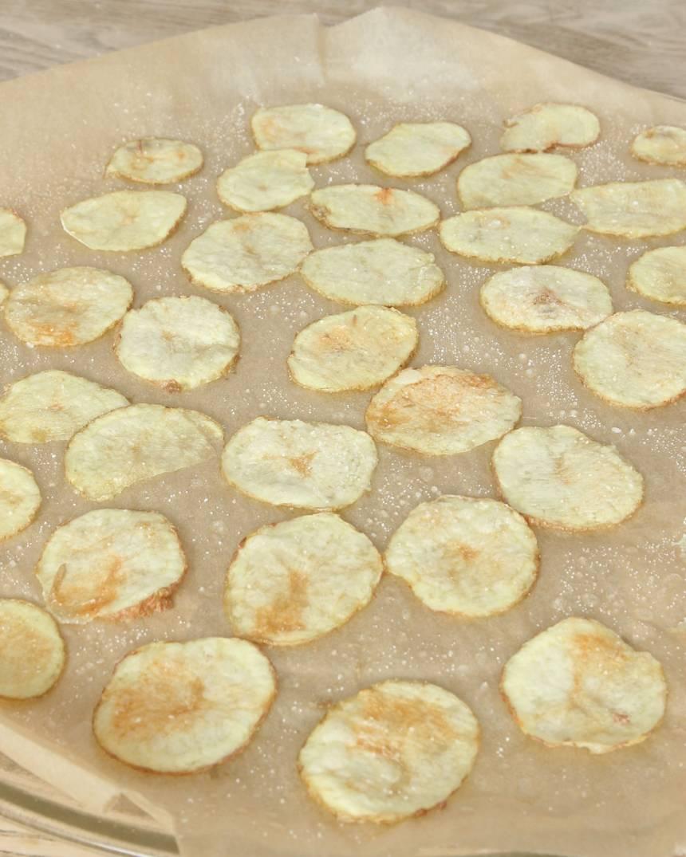 4. Kör potatisarna i mikron i 5–9 min tills de får en gulbrun färg. Tiden varierar beroende på hur många potatisskivor du har och vilken styrka din mikro har. Om du har en liten mikro och bara får plats med en vanlig måltidstallrik får du köra en potatis i taget. Då tar det 3–4 minuter i mikron. Låt potatisarna kallna på pappret.