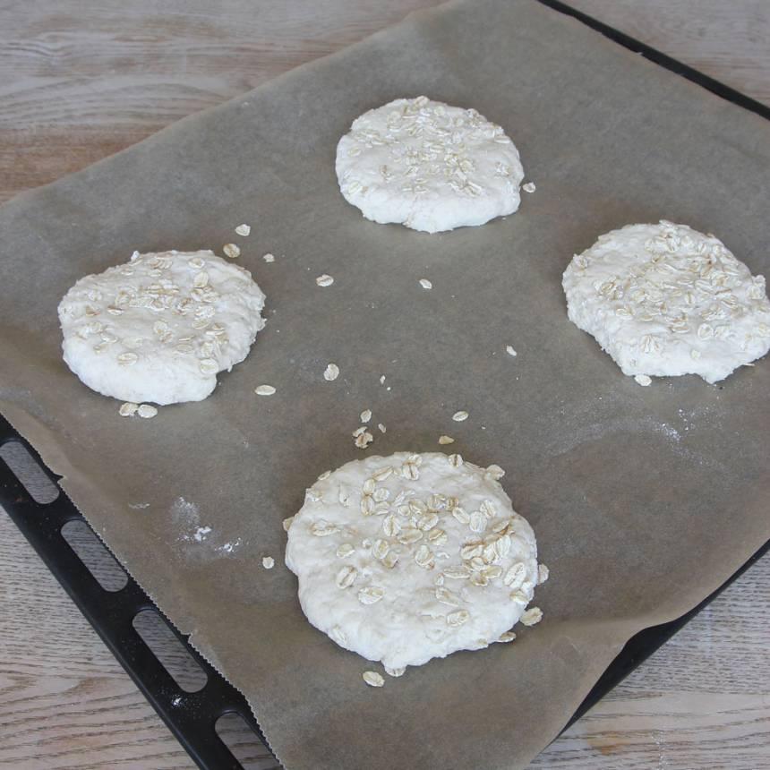 3. Rulla runda bollar av degbitarna med mjölade händer. Strö några havregryn på ytan och platta till dem med händerna på en plåt med bakplåtspapper.