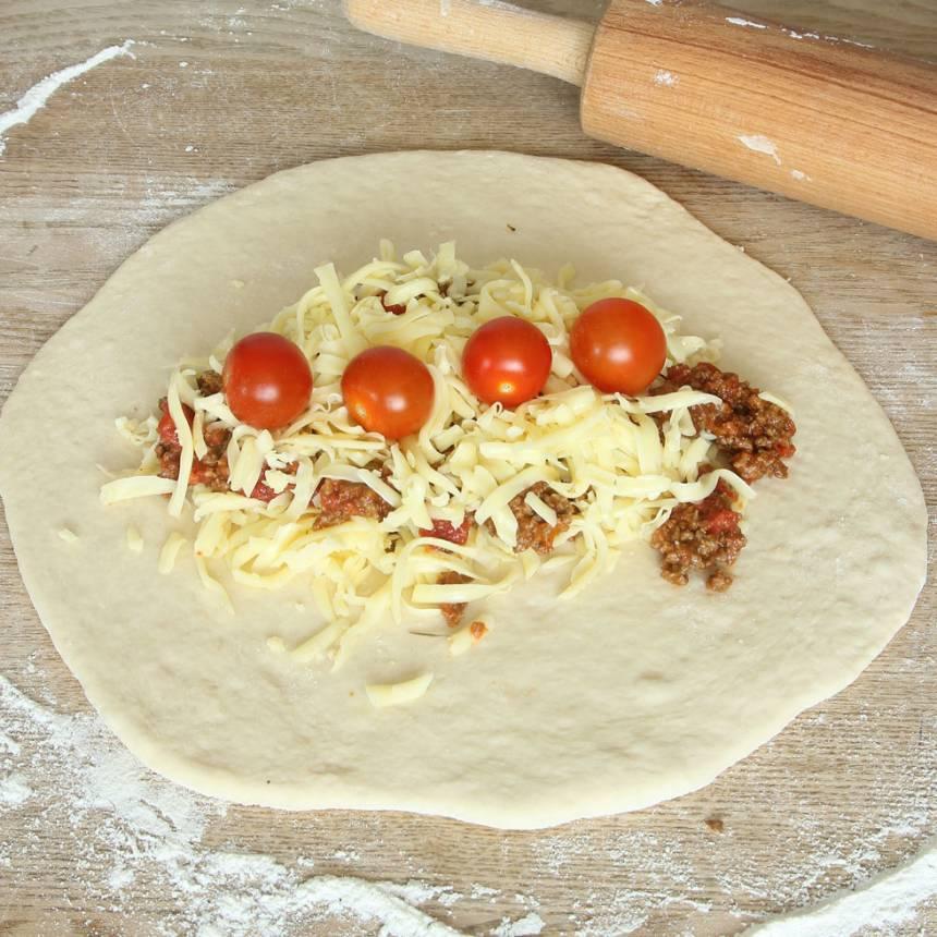 3. Lägg på riven ost, köttfärssås och cocktailtomater. Strö ev. över oregano.