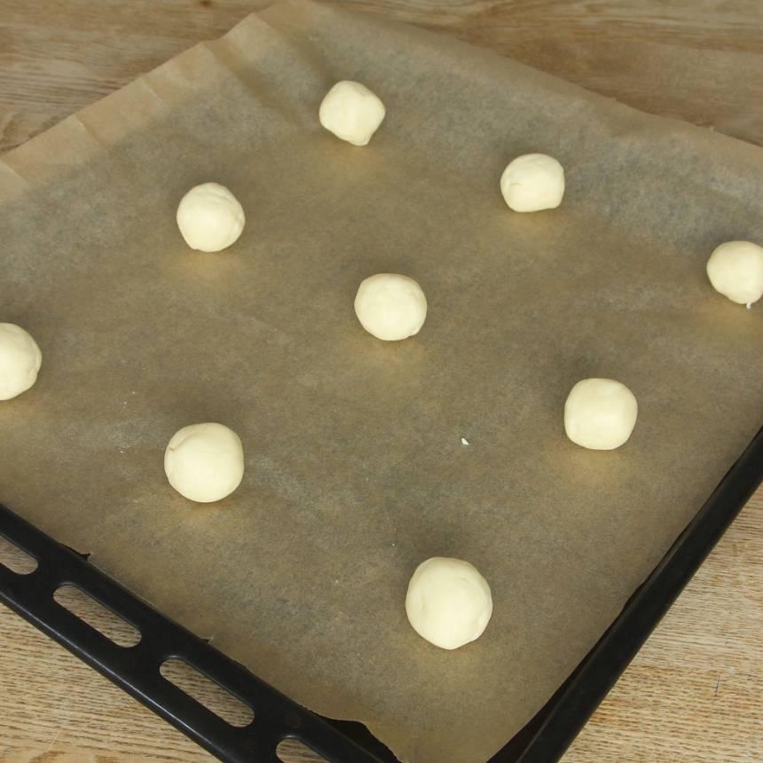 3. Lägg bollarna på en plåt med bakplåtspapper och platta till dem.