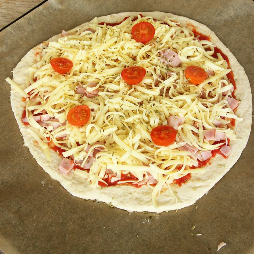 3. Lägg bakplåtspappret med rundeln på en ugnsplåt. Bred ut pizzasåsen på degen. Strö över skinka, riven ost, cocktailtomater och oregano (eller valfri fyllning). Låt pizzan jäsa under bakduk i ca 20 min. Sätt ugnen på 250 grader varmluft.