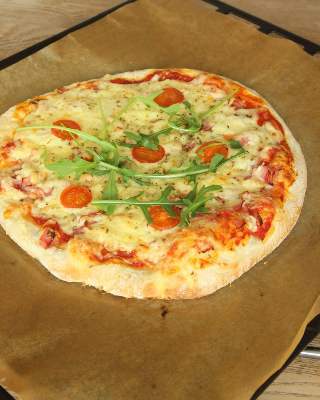5. Lägg några ruccolablad på pizzan före servering.