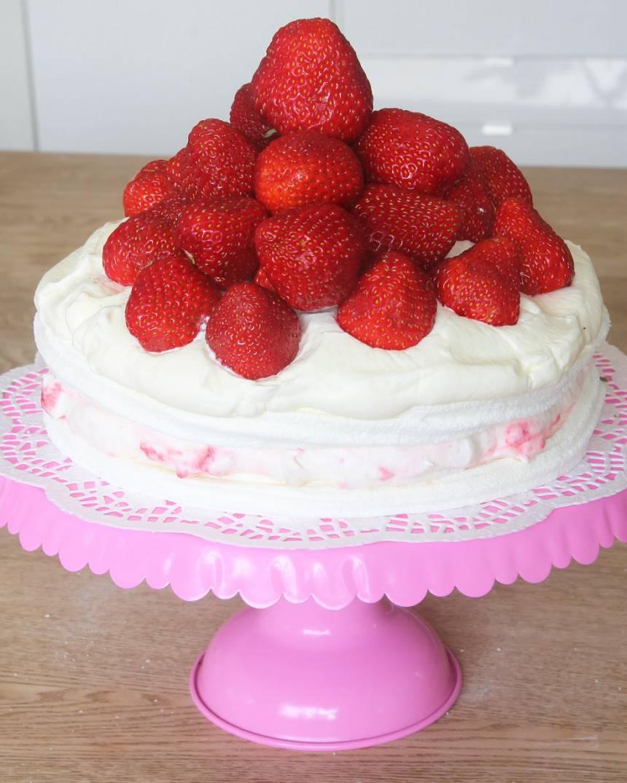4. Bred ut den sista grädden på toppen och garnera med jordgubbar. Pudra ev. över florsocker.