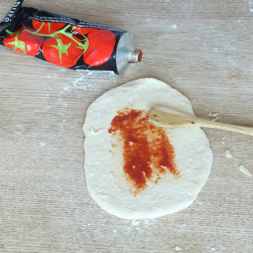 3. Bred ut ett tunt lager tomatpuré på degbitarna.