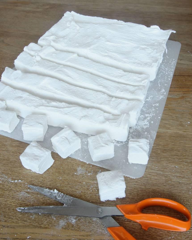7. Vänd på kakan i formen och drag bort bakplåtspapperet. Klipp kakan i fyrkanter med en sax.