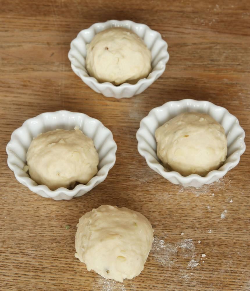 2. Dela degen i ca 16 bitar. Forma runda bollar och lägg dem i muffinsformar av porslin (behöver mjölas) eller papper. Ställ formarna på en ugnsplåt. Låt bröden jäsa under bakduk i ca 30 min. Sätt ugnen på 250 grader.