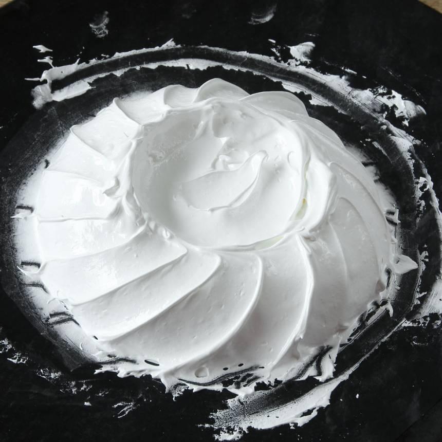 6. Skapa ett mönster på kanten av marängbottnen genom att dra fåror tätt intill varandra runt hela tårtan, med en spatel eller sked, nedifrån botten och snett upp. Forma en grund grop i mitten.