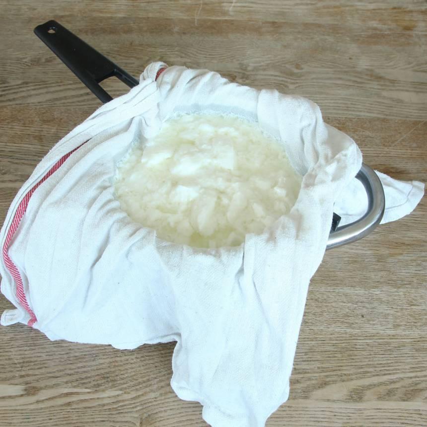 4. Sila bort vätskan från yoghurten. Lägg en ren kökshandduk i ett durkslag. Häll i yoghurten och låt vätskan rinna av.