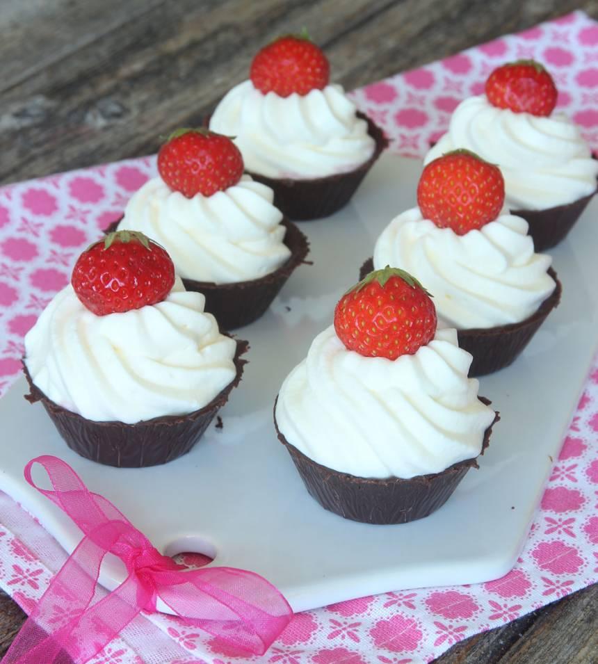 8. Dekorera med en hel eller halv jordgubbe på varje bakelse.