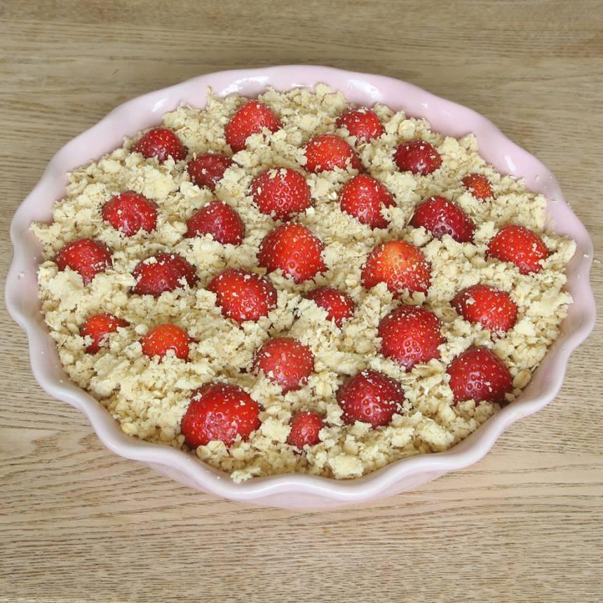 4. Tryck ner jordgubbarna i smuldegen. Strö strösocker över jordgubbarna. Smula ner resten av smuldegen mellan jordgubbarna.