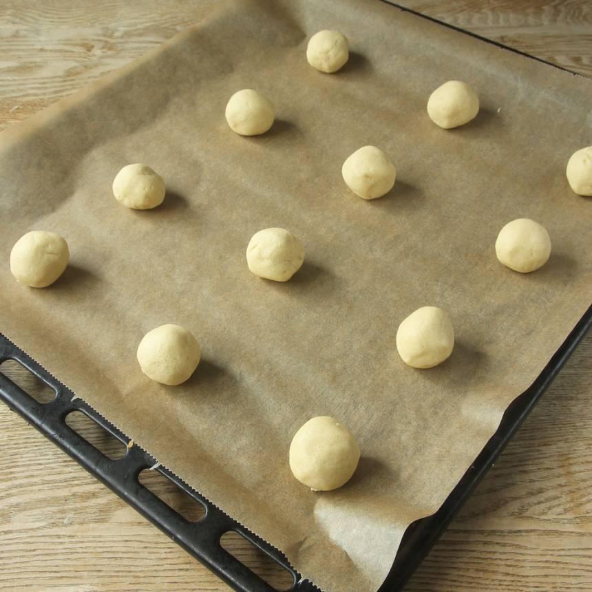 2. Dela degen i ca 30 lika stora bitar. Rulla dem till bollar och lägg dem på en plåt med bakplåtspapper.