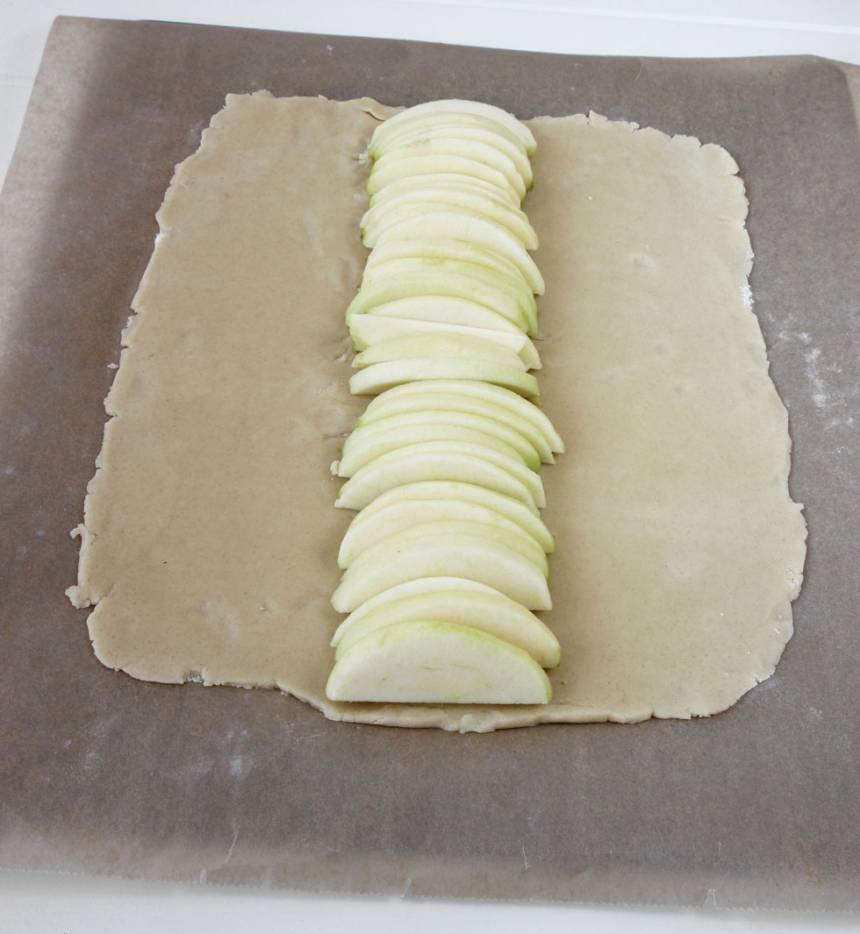 4. Lägg äppelklyftorna i en tät rad i mitten på degen.