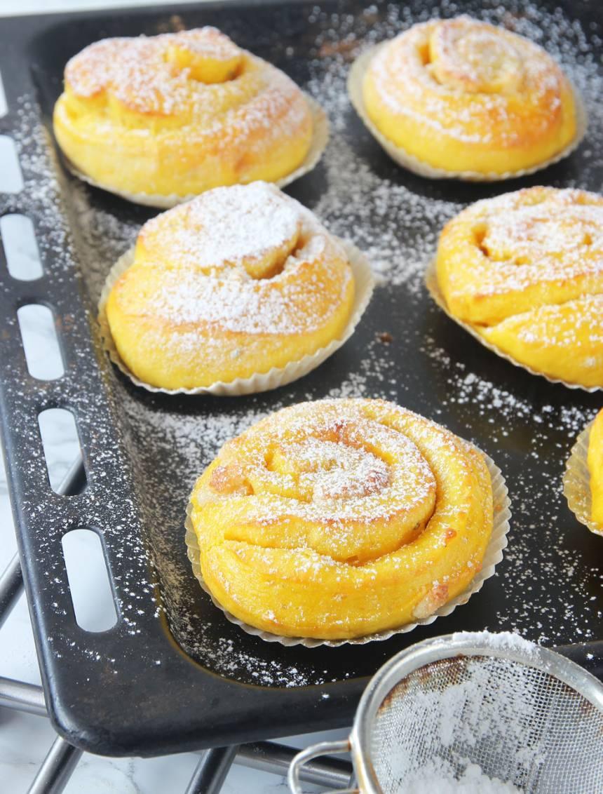 8. Grädda bullarna mitt i ugnen i 7–9 minuter. Låt dem kallna under bakduk på ett galler. Strö över florsocker om du inte använd pärlsocker.