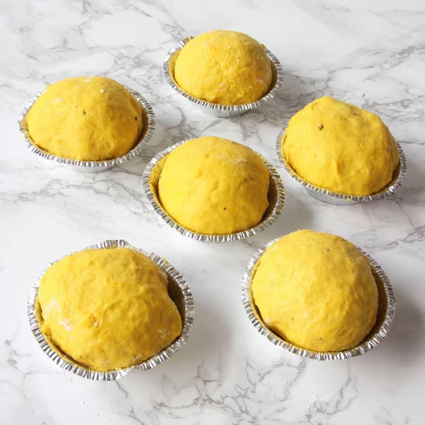 6. Lägg bollarna med skarven nedåt i pappers- eller aluminiumformar på en plåt. Låt dem jäsa under bakduk i ca 30 min. Sätt ugnen på 250 grader.