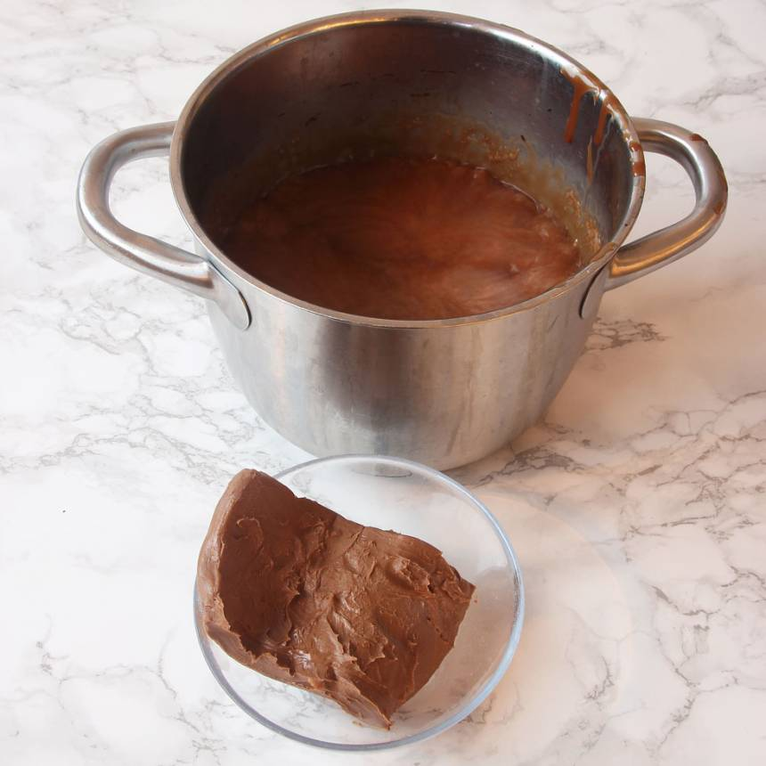 2. Blanda vispgrädde, sirap, strösocker och kakao i en 3–4 liters kastrull. Låt det koka till ca 124 grader. Stäng av värmen och tillsätt nougat och smör. Blanda ordentligt och rör om till en slät smet.