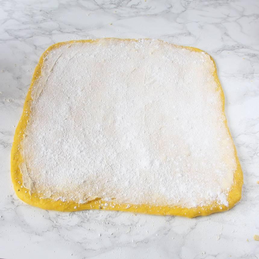 3. Bred ut hälften av smöret på degplattan och strö över hälften av strösockret och vaniljsockret.
