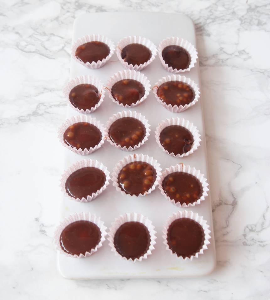 4. Häll kolasmeten ovanpå nötterna i formarna. Fyll dem till ¾. Ställ dem i frysen i några minuter.