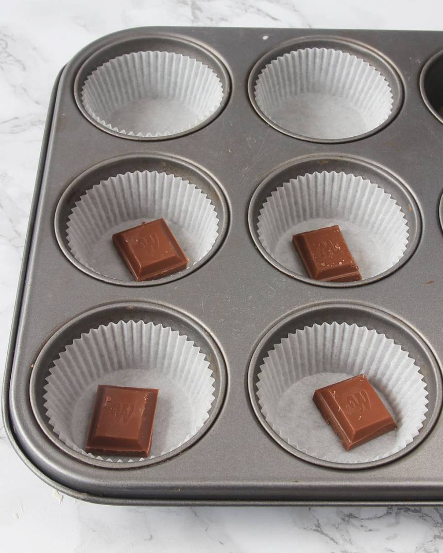 2. Ställ ut 12–15 muffinsformar på en plåt (eller i en muffinsform). Lägg 1 chokladbit i varje form (valfritt).