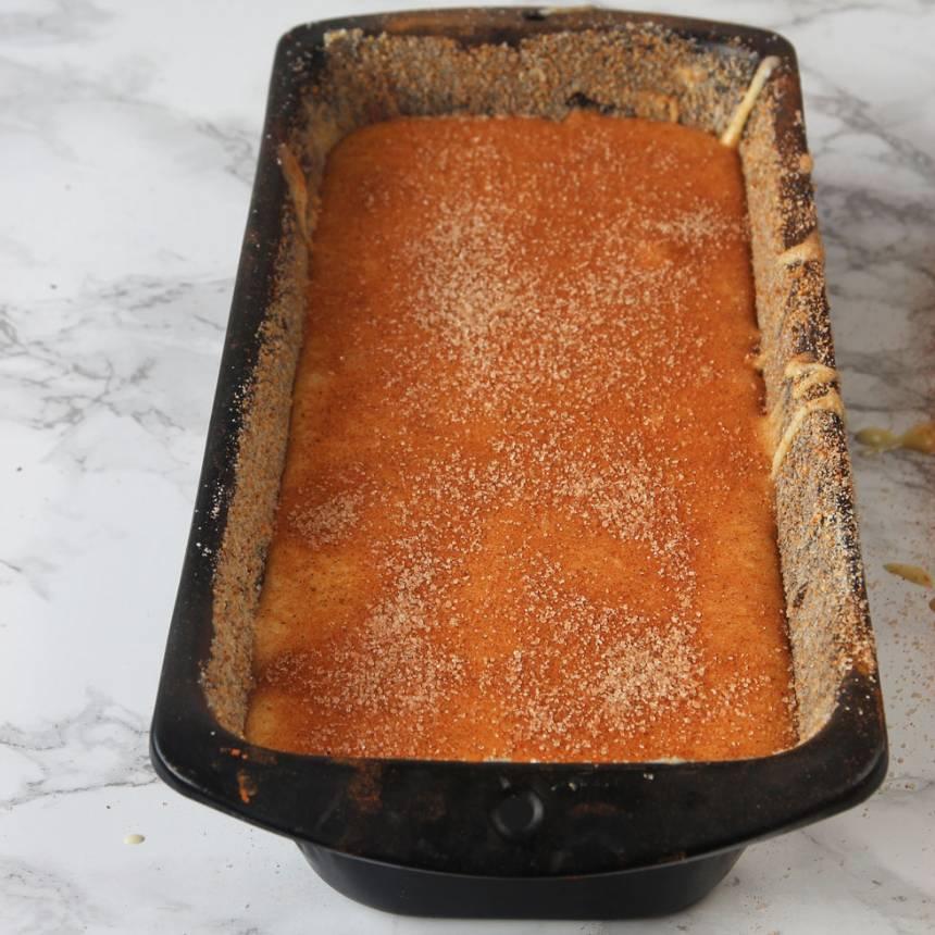 4. Häll över hälften av smeten som är kvar i bunken. Pudra på hälften av kanel- och sockerblandningen. Häll över den sista smeten och pudra över den sista kanel- och sockerblandningen.